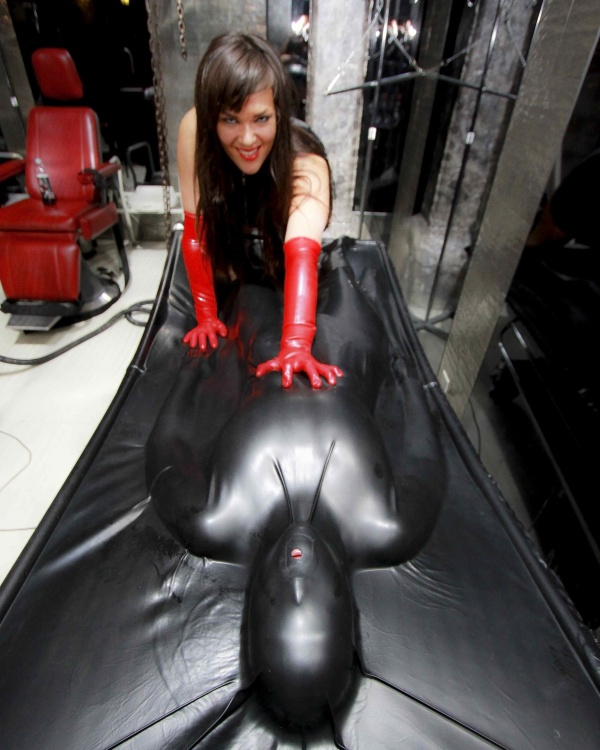 Mistress Leigh w/ Slave in Vacuum Bed